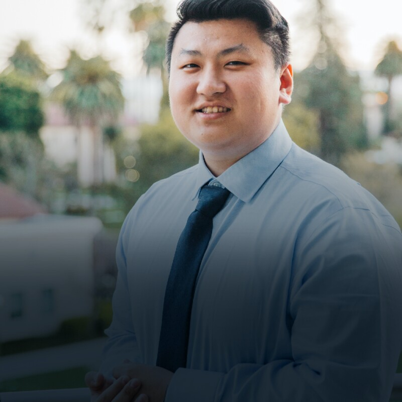 Asian man in a blue shirt and tie smiles