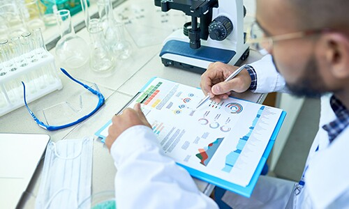 Scientist In Lab Reviewing Data On Clipboard