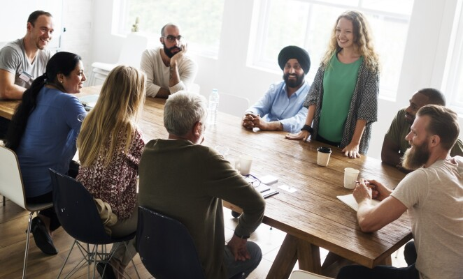 Large team of professionals sit at conference room table, listening to colleague speaking
