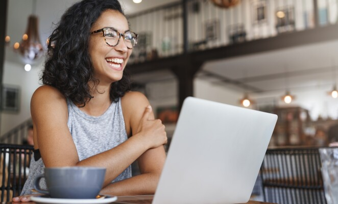 Woman in two story cafe laughs at her table with laptop