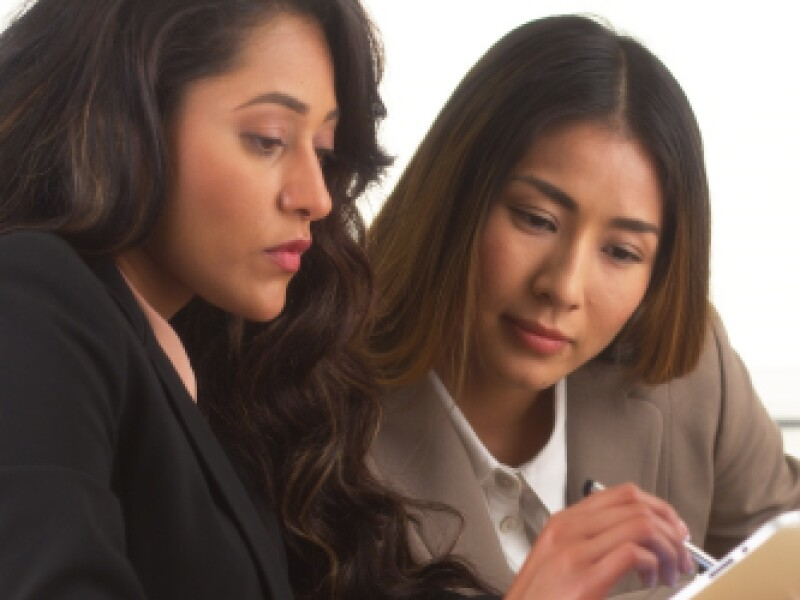 two women in suits looking at i-pad closely