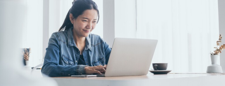 Adult in jean shirt works on laptop at kitchen table