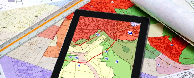 Maps and a tablet screen showing urban and rural landscapes