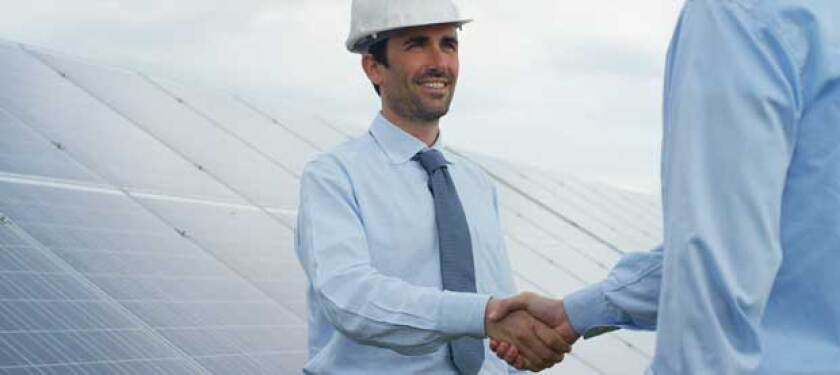 Two businessmen, one in a hard-hat, shake hands in front of a bank of solar panels.