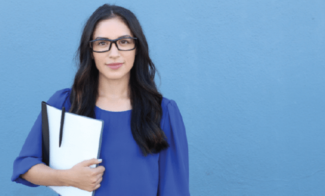 Woman with brown hair wearing glasses holding folder