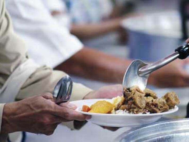 A person serves food to another in a prison cafeteria setting