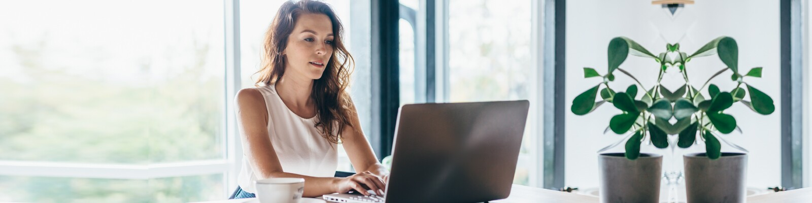 Woman with wavy hair sits in her home working on laptop