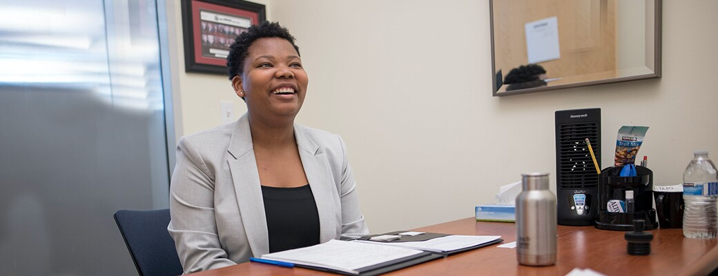 Professional Chico State student wearing a blazer and smiling in her office