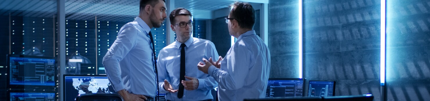 Three professionals in discussion in operations room