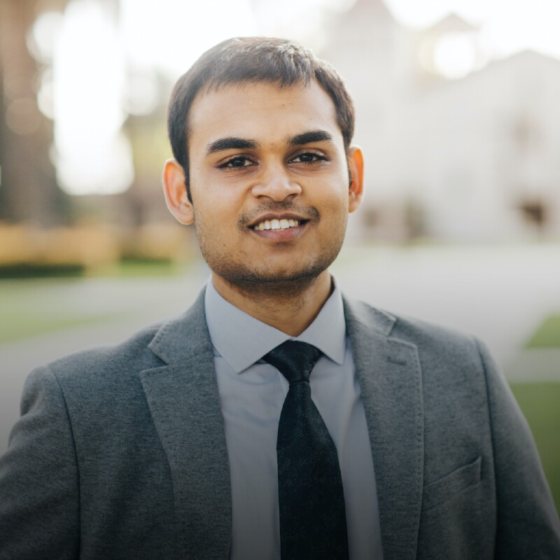 Young Indian male wears a wool gray jacket and black tie