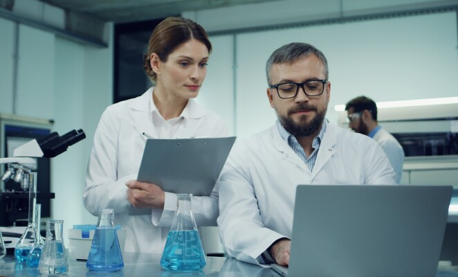 Caucasian man scientist in the white robe and glasses working at the laptop computer over some researching while his female colleague coming with some documents or results and asking something