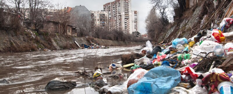 Landfill overflowing into river in an urban environment