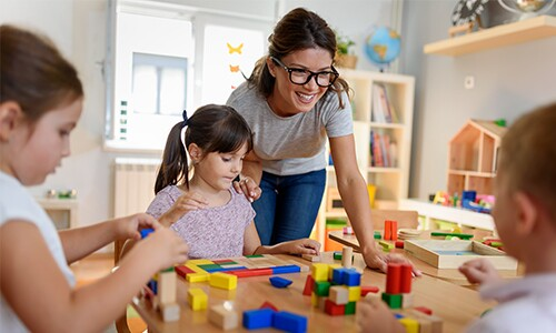 Teacher with glasses with kids at table