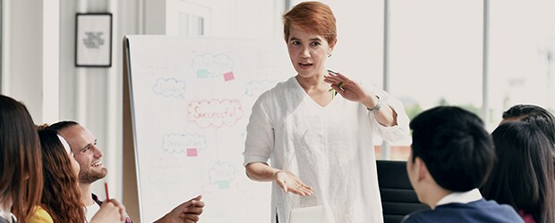 woman-in-white-shirt-with-short-red-hair-gesturing-to-group-in-front-of-white-board-with-red-successful-in-cloud