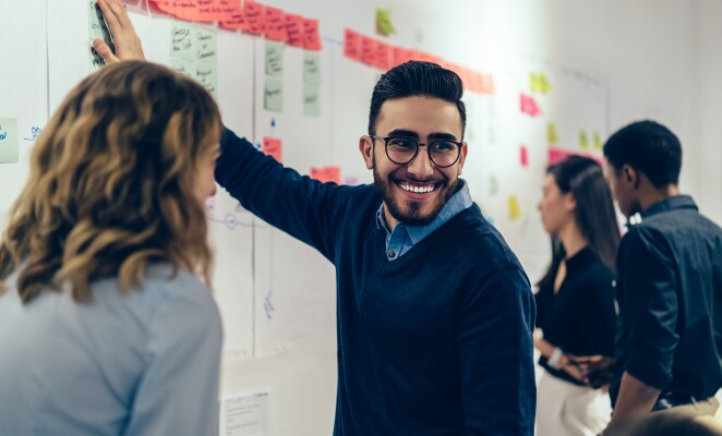 Man with a beard and glasses smiles at coworkers while working at the whiteboard