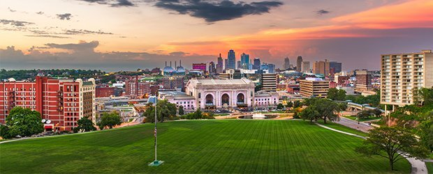 aerial-view-of-campus-city-in-background-at-sunset-green-lawn-in-front