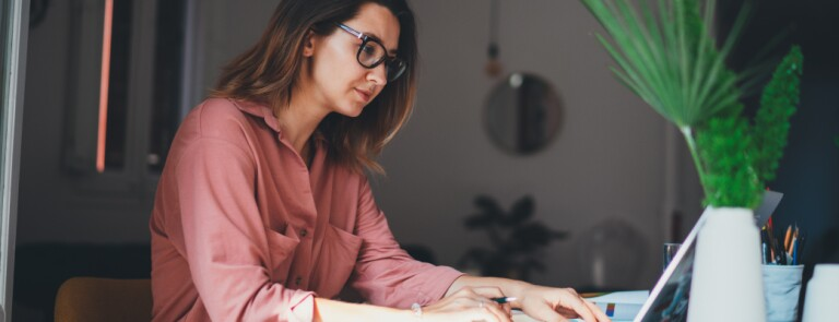 Woman in pink blouse works on her laptop in her home