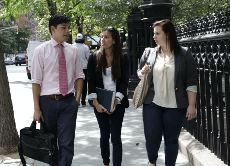three students talk together while walking on a New York City sidewalk