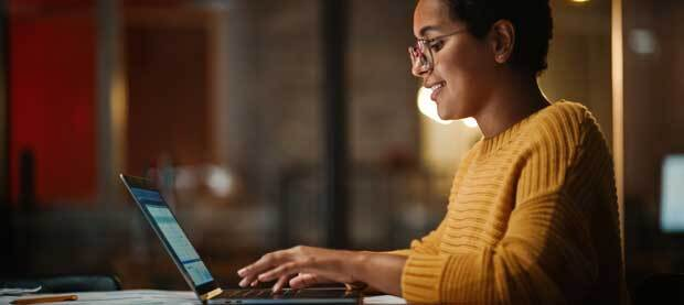 A woman works contentedly at a laptop in a warmly lit room.