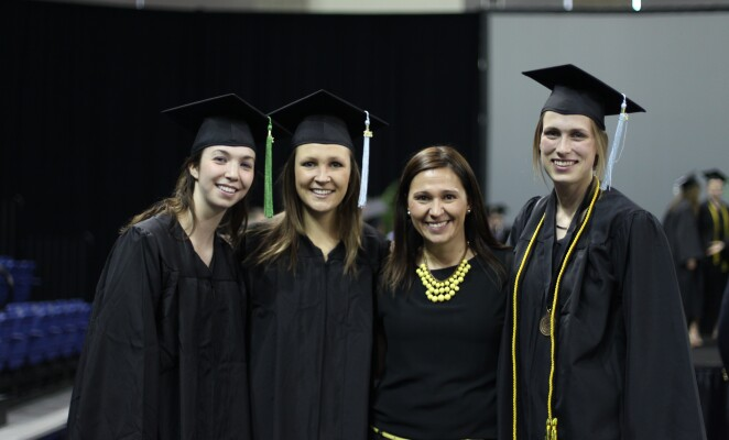 Group of four smiling Marquette graduates in cap and gown