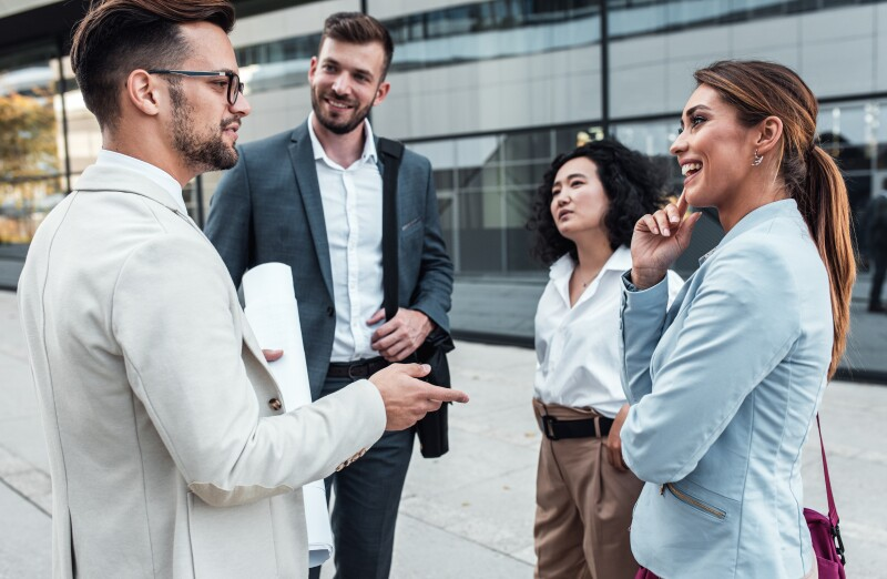 four-people-talking-outside-building-in-suits