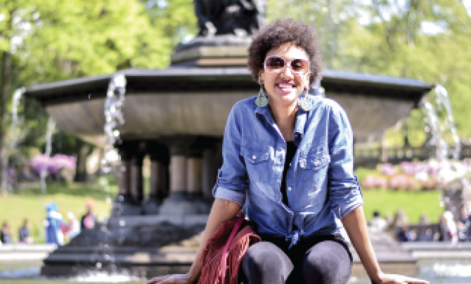 Girl wearing sunglasses sitting by fountain in park