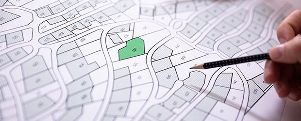 black and white map with one green lot and hand holding pencil above map