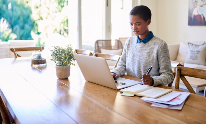 Young professional sits on stool in living room working on laptop