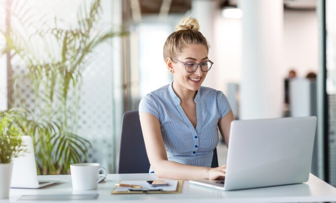 Woman with hair in a bun works on laptop in home office