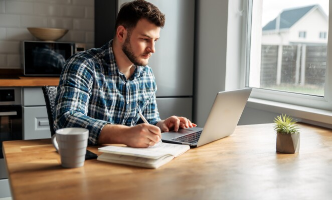 Young professional in plaid sits at desk taking notes from laptop