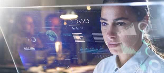 A woman studies graphs on transparent high tech tablet.