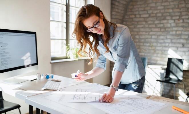 Woman stands over desk assessing paperwork