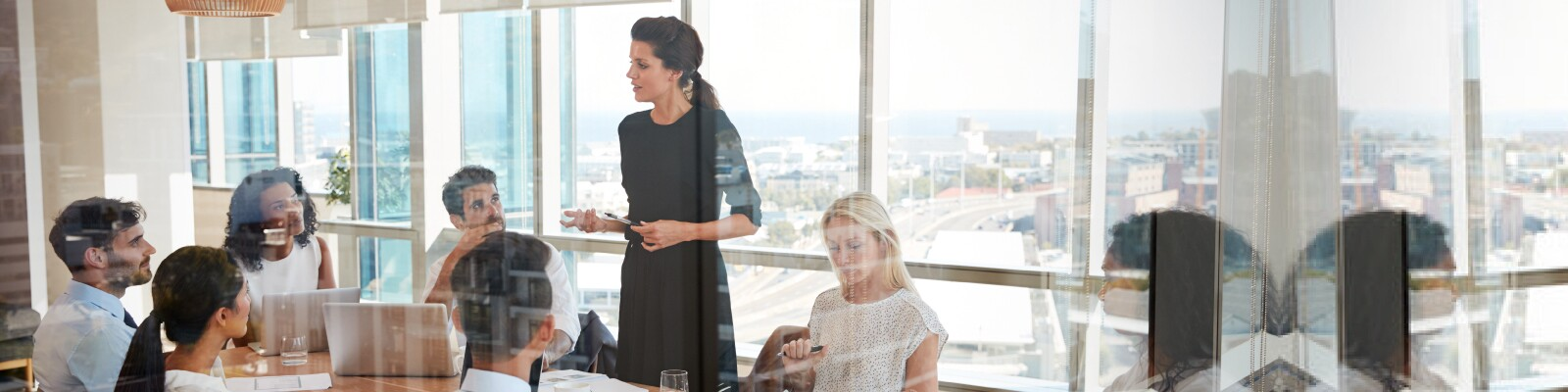 Woman leads a meeting standing up at the table in conference room