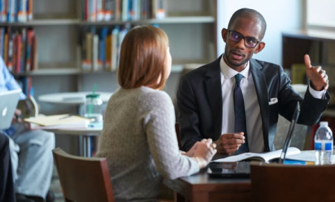 african american man with glasses wearing a suit talking to a woman