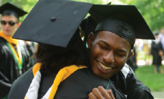 african american couple in graduation gowns hugging