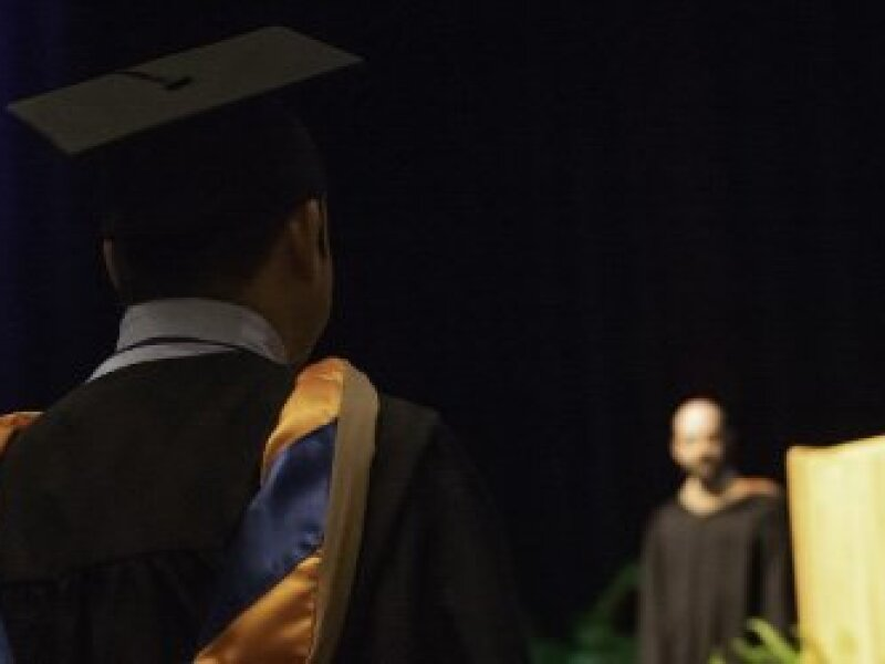 two-MBA-graduates-in-caps-and-gowns-with-backs-to-viewer-and-podium-and-graduation-speaker-in-foreground