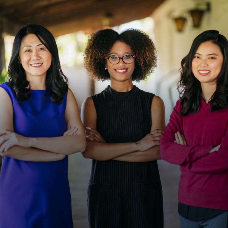 Three SCU students smile on campus