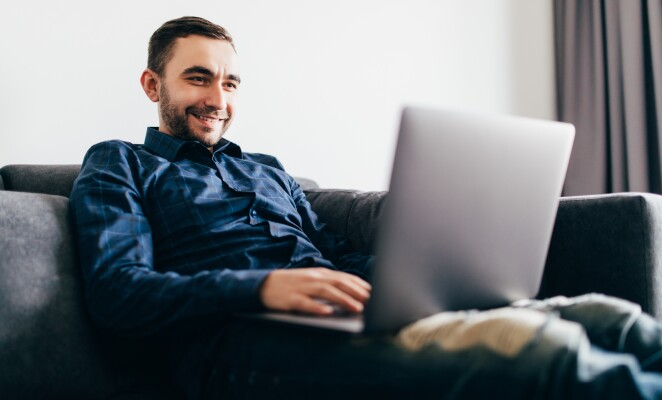 Guy in a denim button down sits on couch while working on laptop