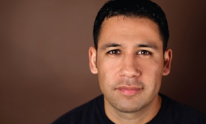 latino man headshot wearing black shirt