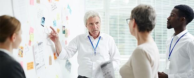 man-in-white-shirt-gesturing-to-whiteboard-speaking-to-three-people
