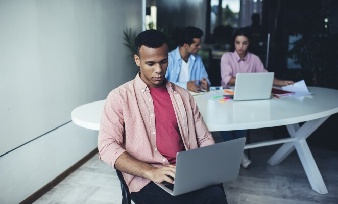 Man sits with laptop in a conference room