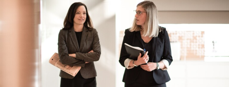 Two Marquette graduate business students walk the hallway together in conversation