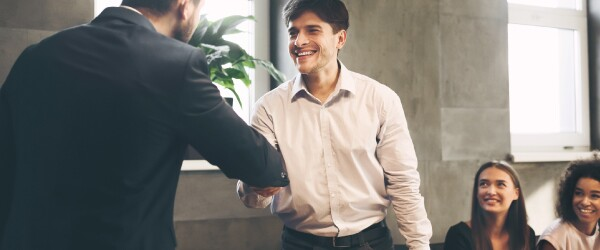 Young professional is congratulated on job promotion