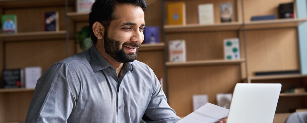 man-with-beard-smiling-at-computer-bookshelves-in-background