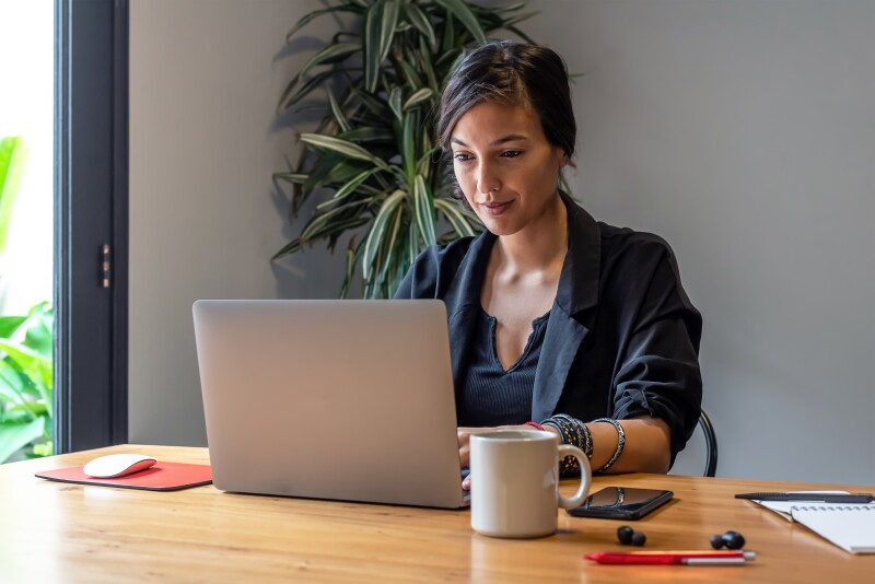 Young woman working online at home with laptop and documents