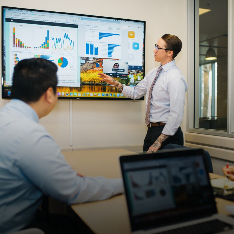 Professional in shirt and tie walks through data on tv screen for coworkers