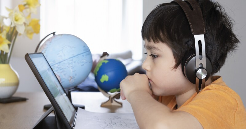Boy in yellow shirt watching laptop globes in the background