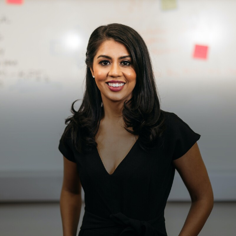 SCU student in black top smiles in front of whiteboard