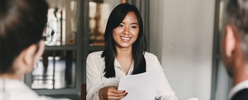 woman in white shirt smiling handing paper to two men