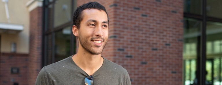 Chico state student smiling in front of building on campus